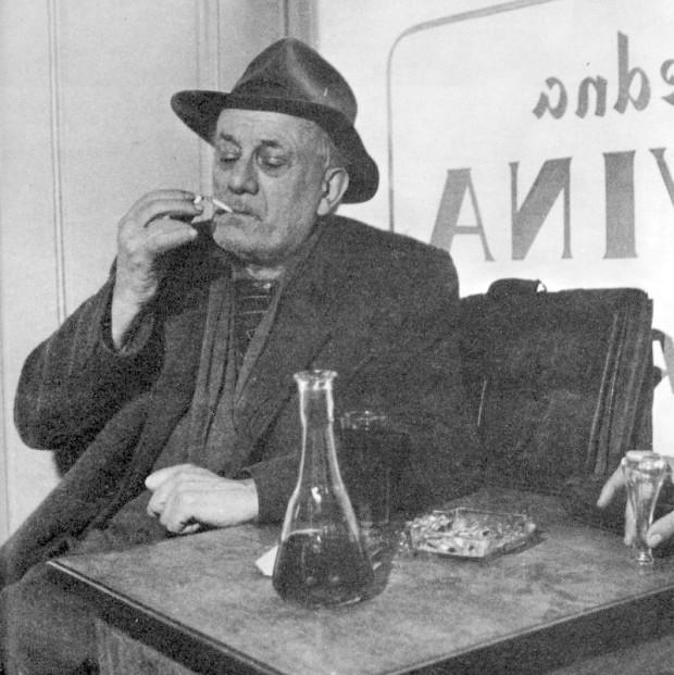 Tin Ujević za stolom u kafani Tip-Top. Ruka u desnom uglu je ruka Miodraga Bulatovića