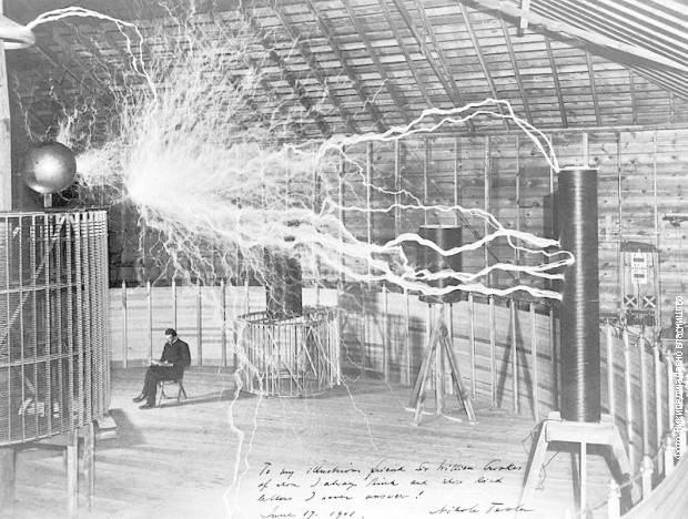 """Tesla u svojoj laboratoriji u Kolorado Springsu unutar svog """"Uveličavajućeg prenosnika"""" koji proizvodi milione volti napona"""